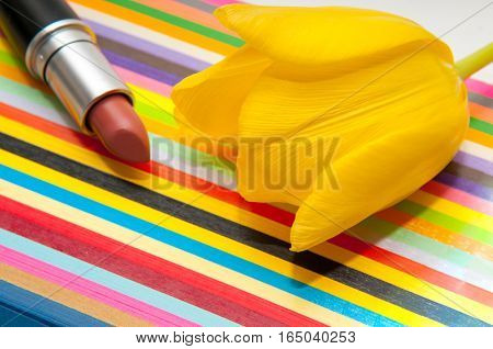 Lipstick Cosmetic Product On A Bright Colorful Striped Background