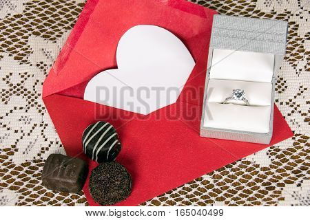 chocolate candy and diamond ring on red envelope with white valentine heart