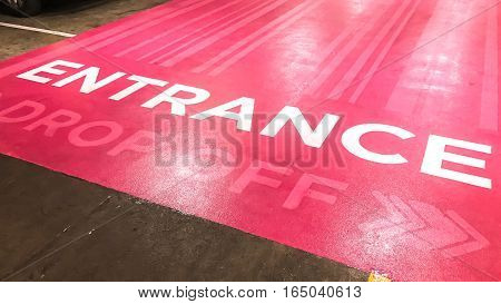 Entrance text and drop off sign on pink floor