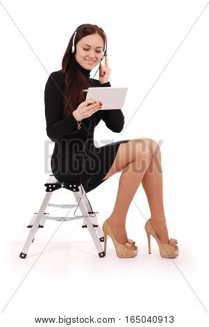 Happy student teenage girl sitting on the ladder looking at tablet pc at headphones isolated on white