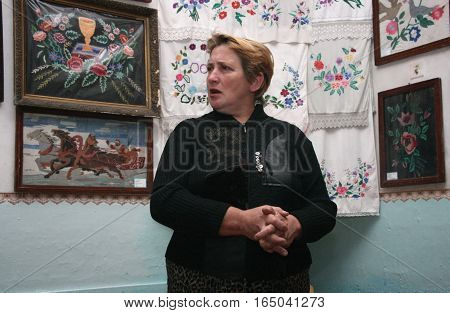 SOFIYIVKA UKRAINE - 15 October 2008: Woman near embroidered towels in rural parlor