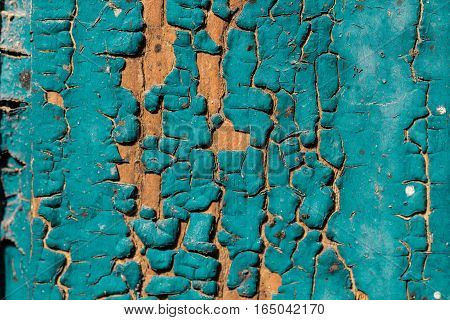 Old blue green cracked paint texture on a wooden background wallpaper