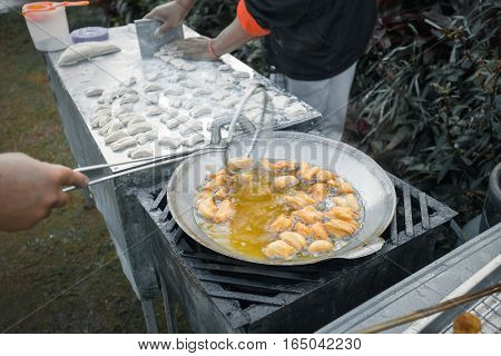 Frying deep fried dough sticks in pan of hot cooking oil. Chef cooking and prepare white raw flour on table beside.