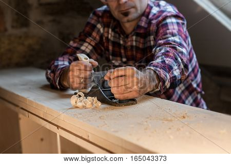 Carpenter works with plane on wooden tabletop