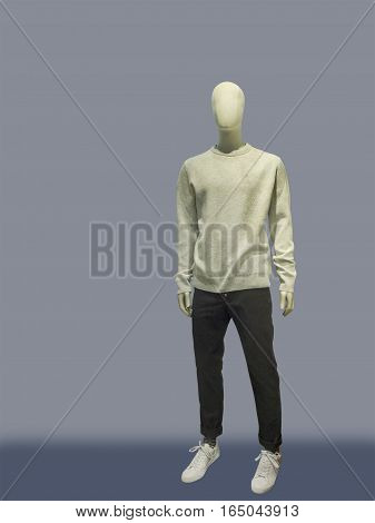 Full-length male mannequin dressed in casual clothes (sweater and trousers) isolated. No brand names or copyright objects.