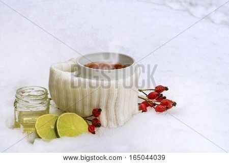Hot tea from red rose hips with lemon and honey in the snow winter vitamin drink against flu and common cold copy space