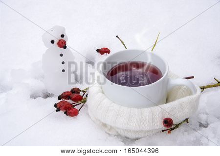 Hot tea with red rose hips in the snow and a little snowman vitamin winter drink as prevention against influenza and common cold selective focus