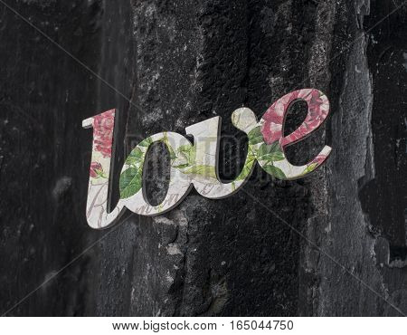 A gentle word love made of wood embellished with flowers on black stone