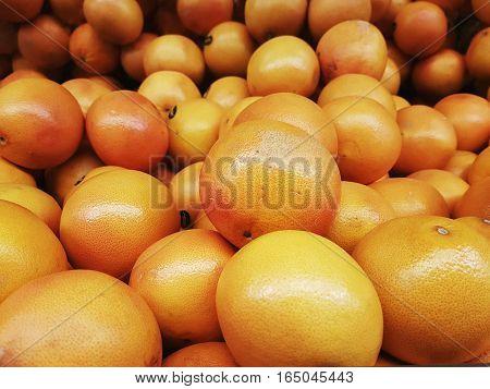 Full frame view of orange grapefruits stacked together on display shelves for sale