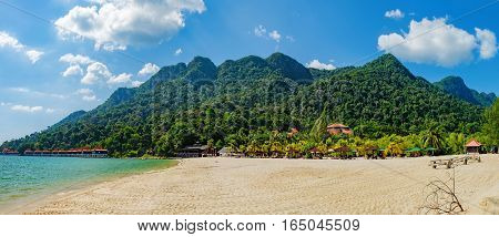 Relaxing on remote paradise beach. Tropical bungalow and luxury house on untouched sandy beach with palms trees in Langkawi Island, Malaysia.