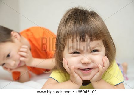 Happy kids smiling little girl with cute cheeks and her brother lying on bed