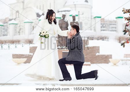 The guy asks the girl hands. Winter wedding, groom on his knee in front of the bride on a snowy street. The concept of marriage, will you marry me.