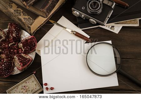 Old vintage camera, books and  juicy garnet near to the blank for letter on dark wooden table