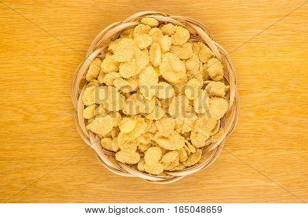 Corn Flakes In Wicker Basket On Wooden Table