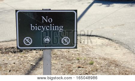 No bike riding sign in public park. Copyright names removed.