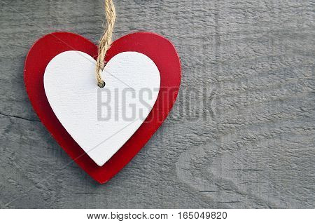 Decorative red and white wooden hearts on a grey wooden background.Two Valentine hearts.Saint Valentine's Day or Love concept.Selective focus.