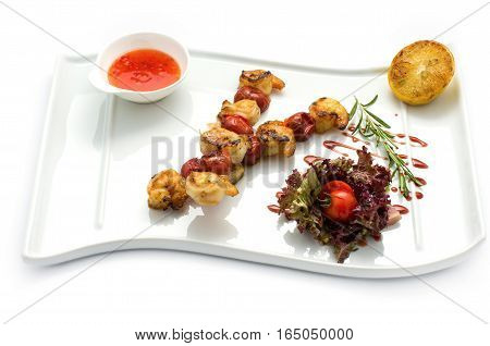 Roasted shrimp's tails on the skewer with lettuce lemon and soy sauce. On a white plate and a white background.