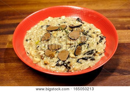 Rice with mushrooms and truffle on wooden table.
