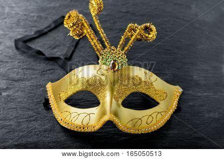 A gold Carnival mask on a black background.