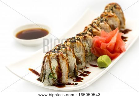 Canadian sushi. Roll made of Fresh Salmon Smoked Eel Cream Cheese and Cucumber inside. Topped with Smoked Eel unagi white background.