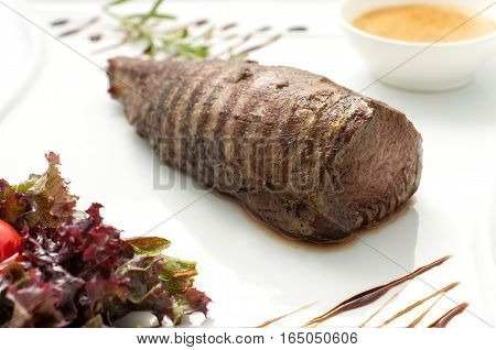Delicious chateaubriand steak . Veal tenderloin cooked grilled on a white plate on a white background isolated