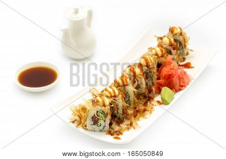 Golden dragon sushi roll is served on a white plate white background with wasabi and ginger