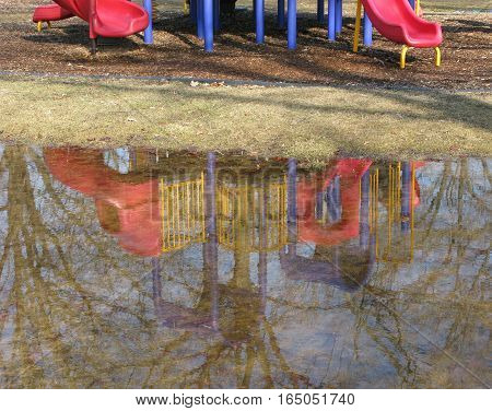 After a heavy rain a large puddle reflects trees and a children's playscape in a playground in the park.