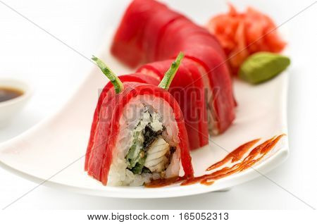 Sushi Red Dragon roll with tuna avocado cucumber and ginger. Traditional asian rice sushi healthy seafood. White plate isolated background