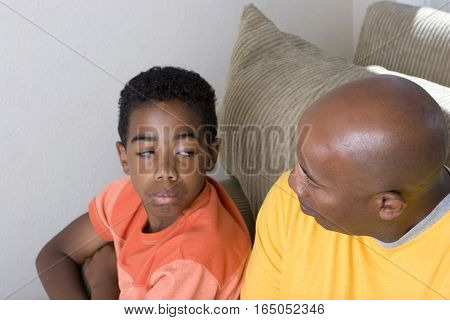 African American father and son arguing at home