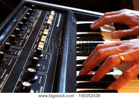 Male Hands Playing A Vintage Analogue Synth In Shallow Focus