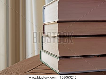 Stack of hardcover books on a wooden table