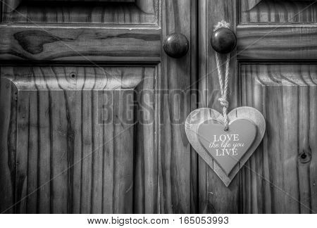 love the life you live wooden heart on old rope string strap on closet wooden door