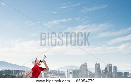 Young man in hat making announcement in megaphone