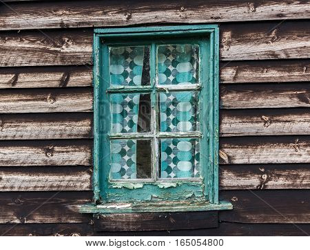 Old window with flaking paint on weathered derelict building