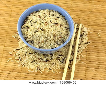 China color rice in blue bowl and chopsticks on brown straw mat closeup