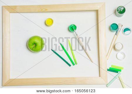 Jars of green pigment with paintbrushes and an apple in a wooden frame