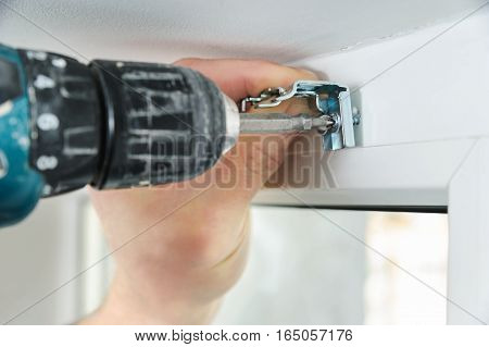Installing wooden blinds. A man attaches to a window metal bracket that holds the jalousie.