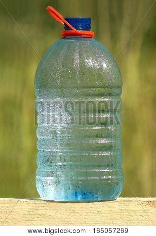 Plastic bottle with cold ecologically crystal pure drinking water outdoor on blur background close up