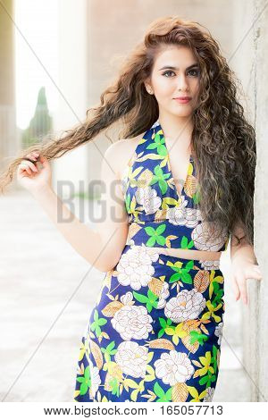 Attractive young fashion model curly woman outdoors, flowery dress. A beautiful, sensual young woman is outdoors leaning against a wall. The girl has a happy expression, one hand touching her hair. Big eyes and perfect makeup. Curly brown hair.
