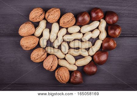 Nuts in the shape of heart on a wooden background
