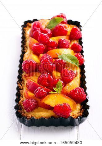 Peach and raspberry cheesecake tart on table
