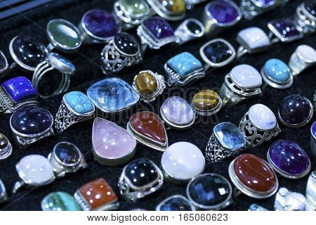 Colorful gems stone rings in a mineral market