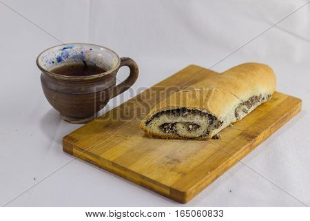 cup of tea and a roll with poppy seeds on a white background. tea and roll with poppy seeds on the board. tea and pastries