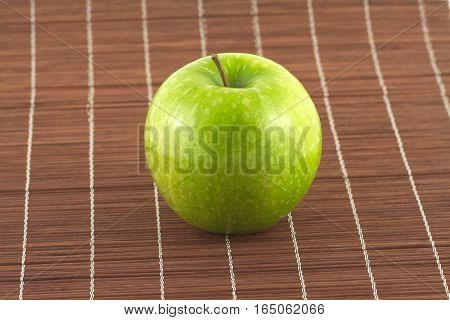 Ripe green apple on brown wicker straw mat close up