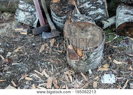 a pile of chopped firewood with axe