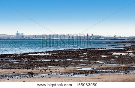 Far panorama of Belfast harbor shipyard Titanic quarter and Belfast Bay viewed over the beach during a low tide.