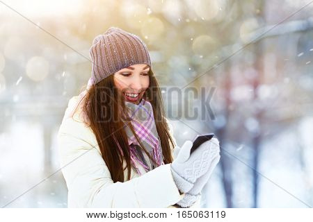Portrait of smiling young woman talking mobile phone in winter park.