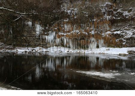 Jagst in the winter / Icicles hang from the bluff to the river