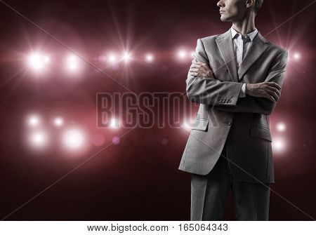Businessman with arms crossed on chest standing in lights of stage