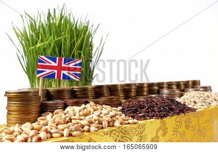 Great Britain Flag Waving With Stack Of Money Coins And Piles Of Wheat And Rice Seeds